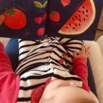 baby reading book with fruits